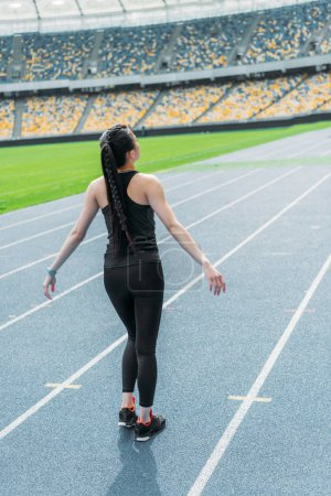 Photo for Back view of young fitness woman in sportswear standing on running track stadium - Royalty Free Image