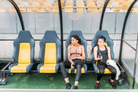 Sportswomen resting on stadium