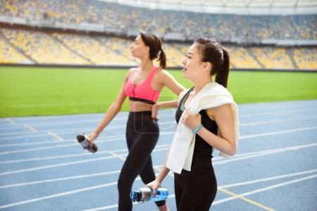 Photo for Tired young sportswomen with bottles of water walking on running track stadium - Royalty Free Image