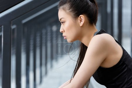 Photo pour Vue latérale de la jeune femme sportive assise sur les escaliers du stade et regardant ailleurs - image libre de droit
