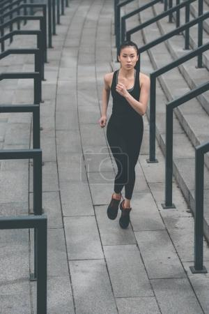 Photo for Young fitness woman in sportswear running on stadium stairs - Royalty Free Image