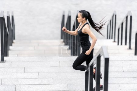 Photo for Side view of attractive young asian woman in sportswear jogging on stadium stairs - Royalty Free Image