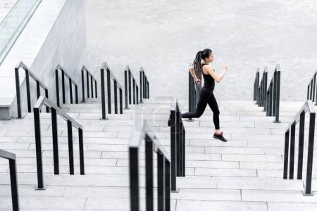 Photo for Side view of sporty young woman jogging on stadium stairs - Royalty Free Image