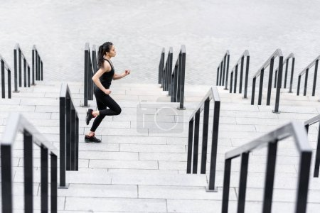 Sportswoman training on stadium stairs