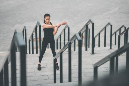 Photo for Attractive young sporty woman exercising and stretching on stadium stairs - Royalty Free Image