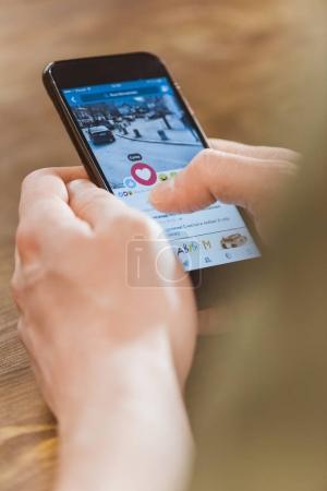 Photo pour Homme utilisant un smartphone avec application facebook à l'écran - image libre de droit