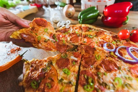 Photo for Hand taking slice of italian pizza with pepperoni on wooden table. Top view - Royalty Free Image