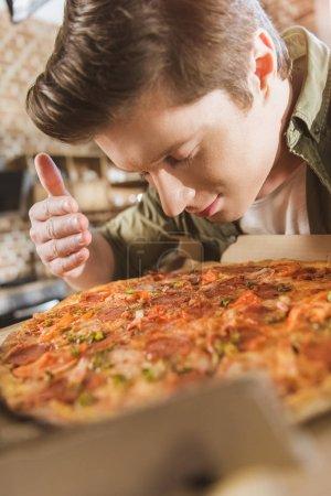 Photo pour Jeune homme appréciant l'odeur de pizza chaude fraîche - image libre de droit