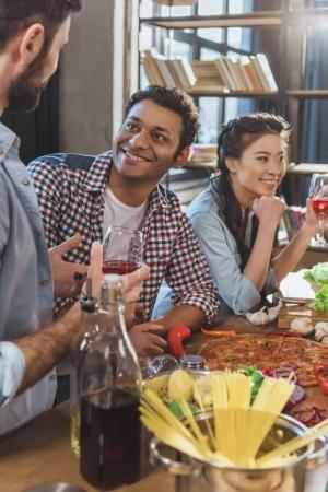 Photo for Young people partying, eating pizza and drinking wine at home party - Royalty Free Image