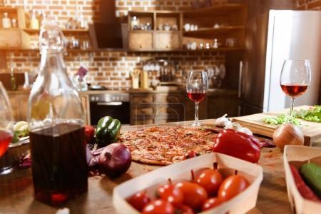 Foto de Mesa de cocina con comida y bebida. Pizza fresca, vino tinto y verduras listo para la fiesta - Imagen libre de derechos