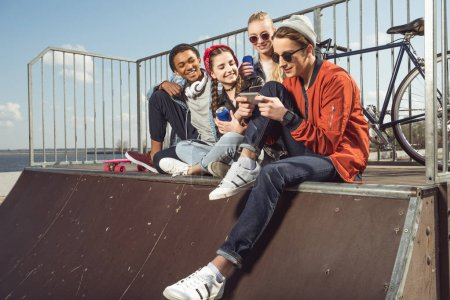 Photo for Teenagers having fun with smartphone in skateboard park, hipster students concept - Royalty Free Image