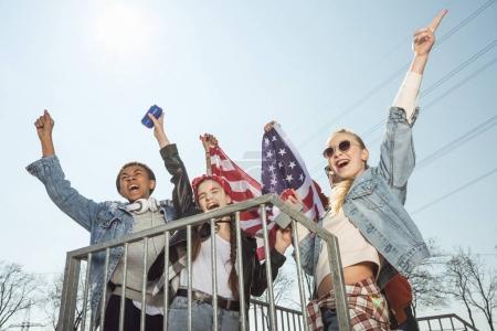 Teenagers waving american flag