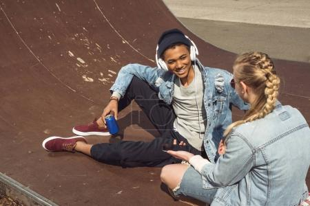Photo for Hipster couple listening music with headphones and siiting in skateboard park, teenagers having fun concept - Royalty Free Image