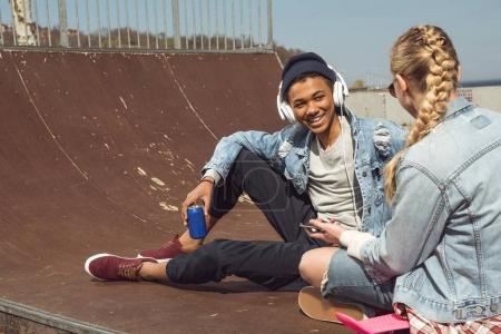 Photo pour Couple hipster écouter de la musique avec écouteurs et siiting dans le parc de skateboard, les adolescents ayant concept amusant - image libre de droit