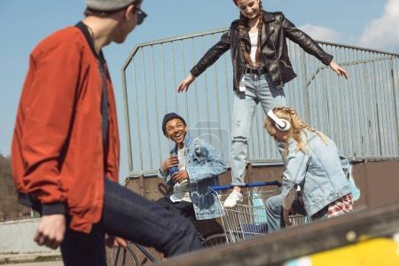 Photo pour Les adolescents s'amusent avec le panier dans le parc de skateboard, concept de style hipster - image libre de droit