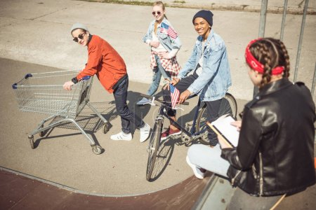 Teenagers with shopping cart and bicycle