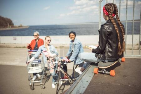 Photo pour Vue arrière d'une adolescente utilisant une tablette numérique et assise sur une planche à roulettes dans un parc de skateboard, concept de style hipster - image libre de droit
