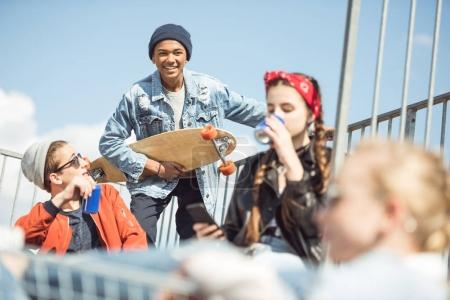 Photo pour Groupe d'adolescents heureux s'amuser ensemble sur la rampe au parc de skateboard - image libre de droit