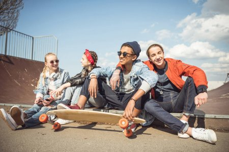 Photo for Happy teenagers group sitting together and talking at skateboard park - Royalty Free Image