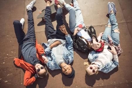 Photo for High angle view of teenagers group lying together and resting at skateboard park - Royalty Free Image