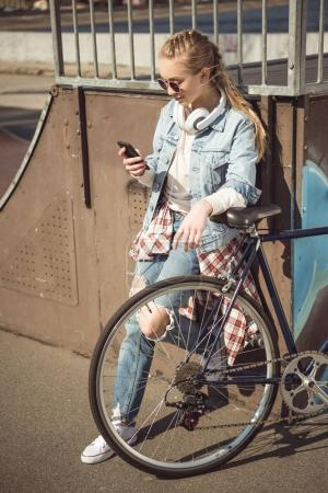 Mädchen mit Fahrrad mit Smartphone