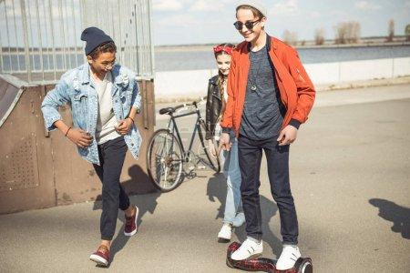 Photo pour Élégant hipster garçon équitation gyroboard avec des amis à proximité, les adolescents ayant concept amusant - image libre de droit