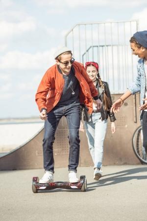 Photo pour Adolescent élégant garçon équitation gyroboard avec des amis à proximité, concept de style hipster - image libre de droit
