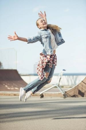 Photo for Stylish teenage girl jumping at skateboard park, hipster style concept - Royalty Free Image
