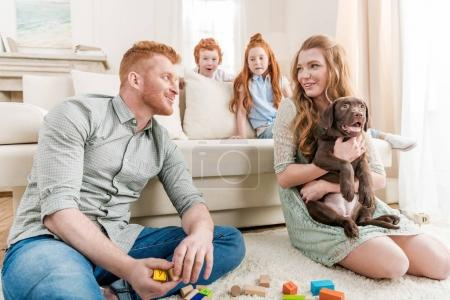 Photo for Beautiful redhead family with puppy playing with constructor on floor at home, family fun at home concept - Royalty Free Image