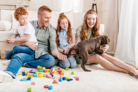 family playing with puppy