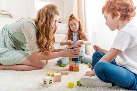 Photo for Beautiful redhead family playing with constructor on floor at home, family fun at home concept - Royalty Free Image