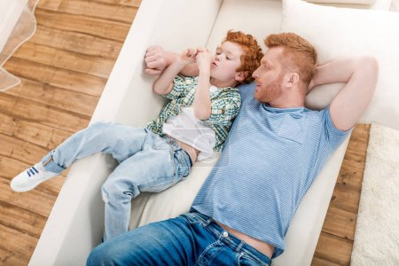 Photo for High angle view of happy father and son lying together on sofa at home, family fun at home concept - Royalty Free Image