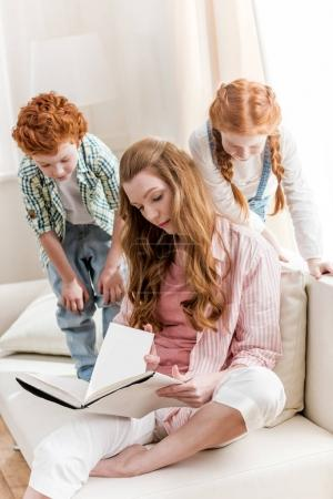 Mother with kids reading book