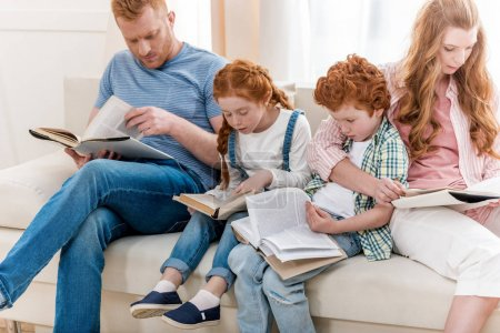 Photo for Beautiful redhead family sitting on sofa and reading books together, big family portrait - Royalty Free Image