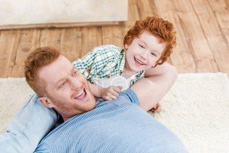 Photo pour Joyeux roux père et fils jouant ensemble sur le tapis à la maison, amusant en famille à la maison concept - image libre de droit