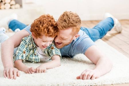 Photo for Happy redhead father and son having fun together on carpet at home, family fun at home concept - Royalty Free Image