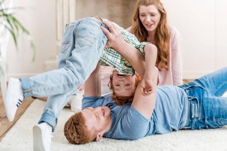 Photo pour Heureux parents jouer avec adorable rousse fils à la maison, amusant en famille à la maison concept - image libre de droit