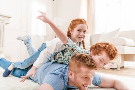 Photo pour Père heureux avec des enfants rousses adorables jouant et s'amusant ensemble sur le sol, amusant en famille à la maison concept - image libre de droit