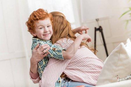 Photo pour Mère et petit fils souriant se serrant dans leurs bras - image libre de droit