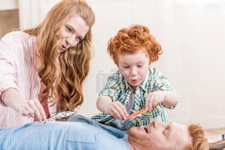 Foto de Los padres y el pequeño hijo jugando con juguetes en el hogar, diversión familiar en el concepto de hogar - Imagen libre de derechos