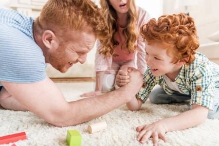 Photo pour Vue latérale du père et du fils jouant au bras de fer avec la mère à proximité, concept de plaisir familial à la maison - image libre de droit