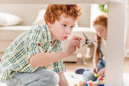 Photo pour Petit garçon jouant avec la peinture bleue tout en jouant avec des cubes de soeur - image libre de droit