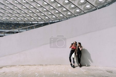 Sportswomen resting on stadium