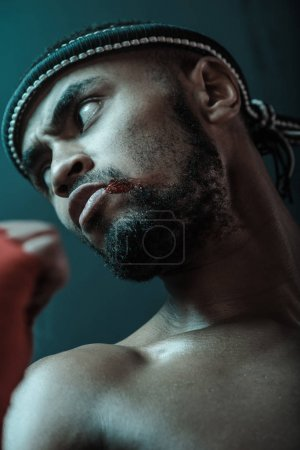 Photo for Close-up portrait of determined Muay thai fighter with blood on face looking away, ultimate fight concept - Royalty Free Image