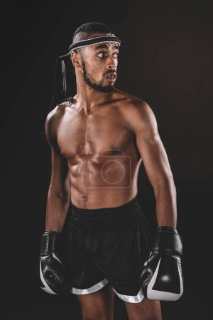 Photo for Portrait of young shirtless Muay thai fighter with boxing gloves looking away, action sport concept - Royalty Free Image
