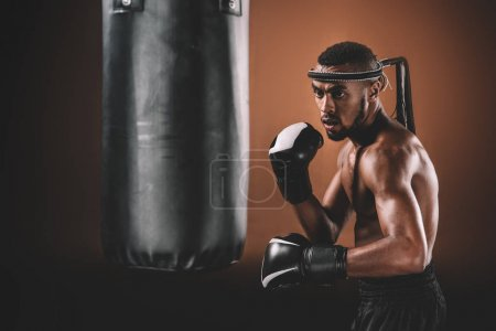 Photo for Determined young Muay Thai fighter in boxing gloves training thai boxing with punching bag, boxing gloves fight concept - Royalty Free Image