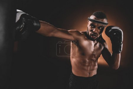 Photo for Determined young Muay Thai fighter in boxing gloves training thai boxing with punching bag, action sport concept - Royalty Free Image