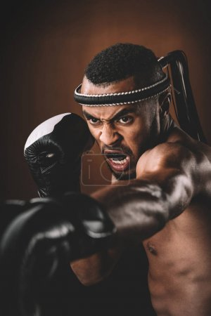 Photo for Aggressive young Muay Thai fighter in boxing gloves training thai boxing, action sport concept - Royalty Free Image