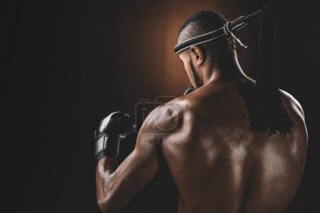 Photo for Back view of shirtless Muay Thai athlete standing in studio, action sport concept - Royalty Free Image