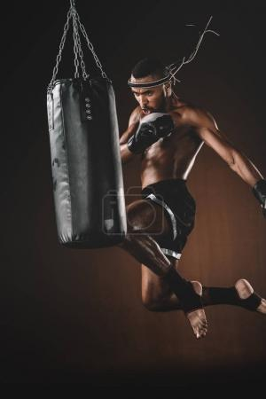 Photo for Concentrated young sportsman jumping and thai boxing with punching bag, boxing gloves fight concept - Royalty Free Image